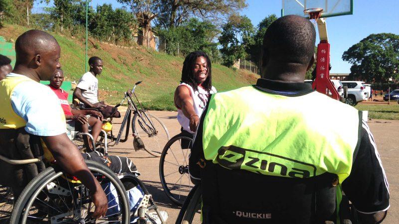 Gros plan sur quelques-uns des membres de l'équipe masculine ougandaise en fauteuil roulant s'entraînant sur un terrain de basket