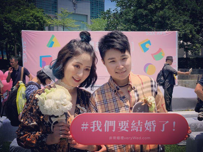 Un couple taiwanais pose avec un bouquet de fleurs et un panneau rose célébrant leur mariage après la légalisation des unions pour les personnes de même sexe à Taïwan.