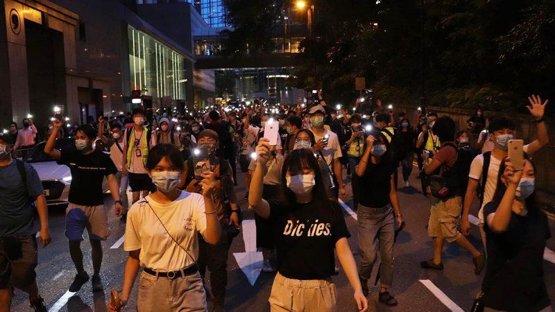 Une foule de manifestants à Hong Kong marche dans les rues, brandissant des téléphones portables dont la lampe torche est allumée.