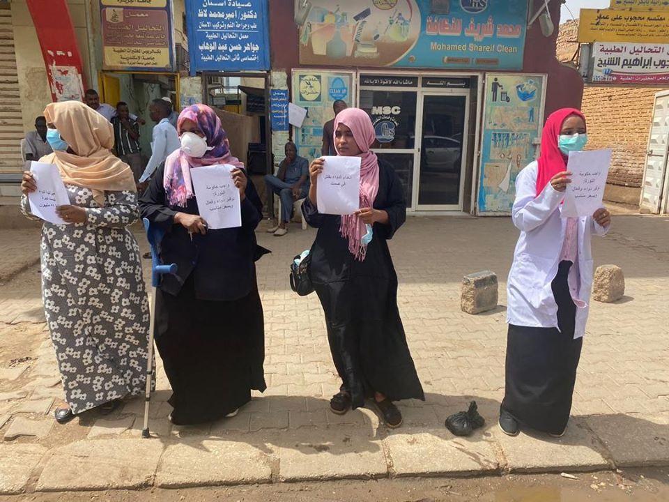 Quatre pharmaciennes soudanaises portent des pancartes A4 pour protester contre la crise de la pénurie de médicaments dans le pays.