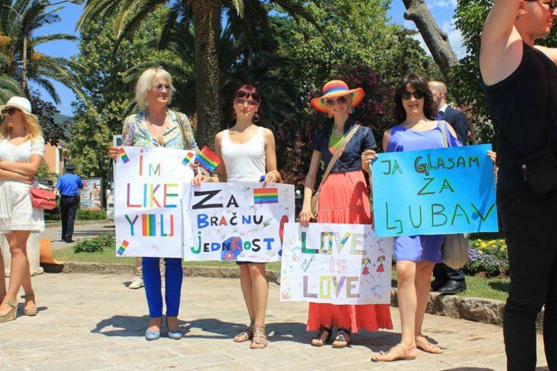 Quatre femmes tiennent des panneaux aux couleurs arc-en-ciel, en soutien au mariage pour tous au Monténégro.