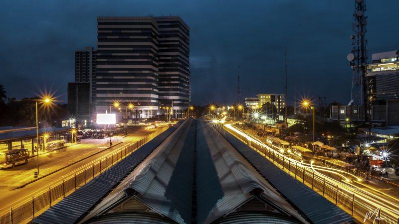 Vue d'une station du Dar Rapid Transit de nuit. Des bus circulent sur une voie réservée.