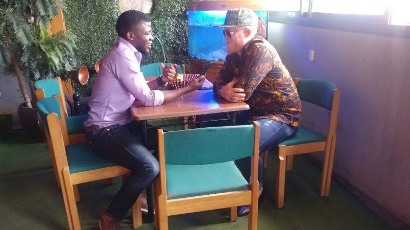Le promoteur musical camerounais Mola Mongombe pendant l'enregistrement de l'entretien avec l'auteur. Ils sont assis à une table de restaurant.