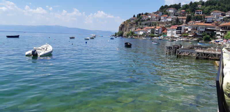 Embarcations sur les eaux calmes du lac d'Ohrid et maisons du 19e siècle implantées sur les berges.