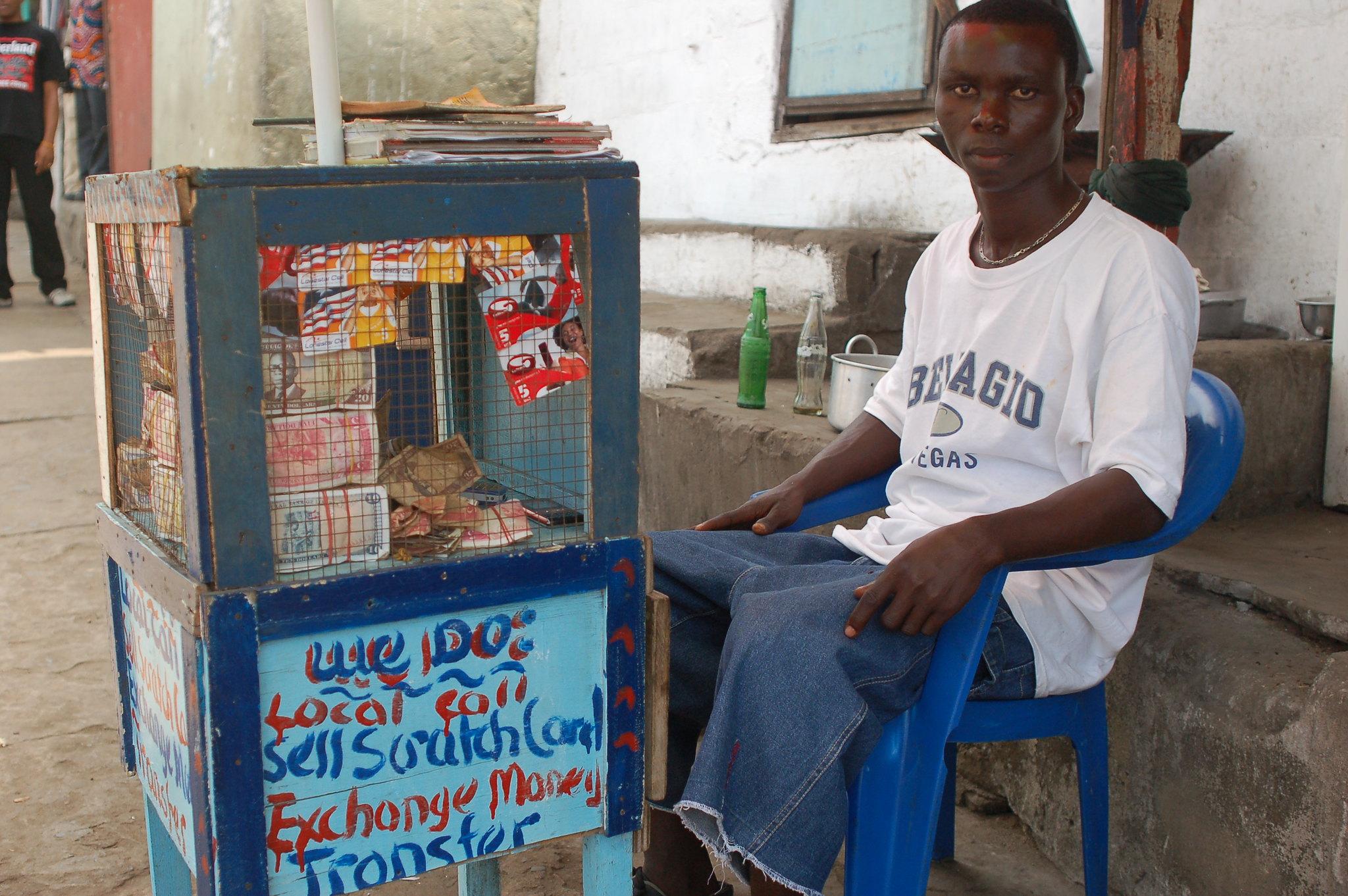 Le vendeur est assis devant un petit kiosque qui propose des cartes de recharge pour téléphone portable.