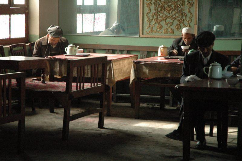 A l'intérieur d'une maison de thé, trois hommes sont assis, chacun à une table et tout en lisant, ils savourent le thé. Sur chaque table, il y a une théière et une tasse.