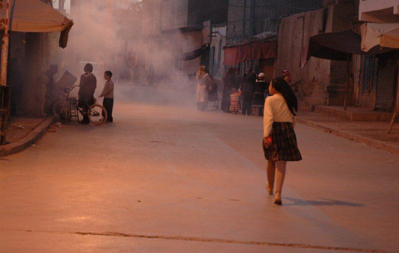 Dans une rue de Kashgar, la nuit. En premier plan, une jeune femme de dos, en jupe et pullover, qui marche. Plus loin, de petits groupes devant des échoppes, obscurcies par la fumée.