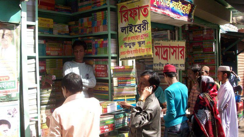 Un étal de livres dans le vieux Dhaka vendant principalement des manuels scolaires. De nombreux livres colorés remplissent les étagères et sept personnes sont devant l'étal. Le vendeur est adossé a l'étagère, bras croisés.