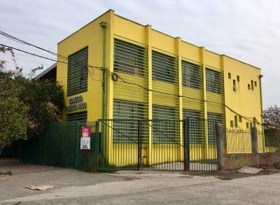 Une école municipale fermée au Chili. Le bâtiment est jaune et ses volets métalliques sont descendus, la rue est déserte.