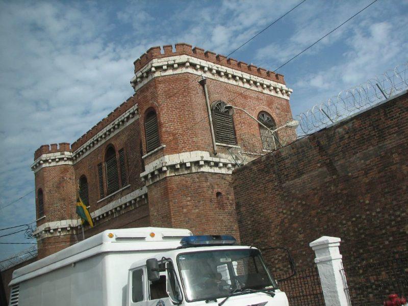 Derrière un fourgon de transport de prisonniers, les hauts murs en brique rouge de la prison de Tower Street.