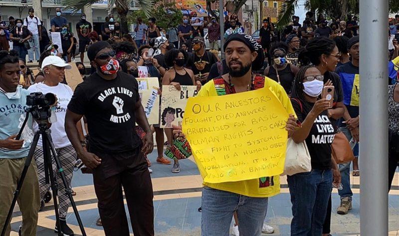 Une foule de manifestants est rassemblée, pour certains portant des pancartes avec leurs revendications.