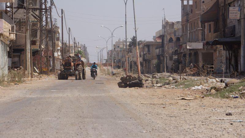 On aperçoit un tracteur et une moto, seul traffic dans une rue désertée de la ville de Deraa.