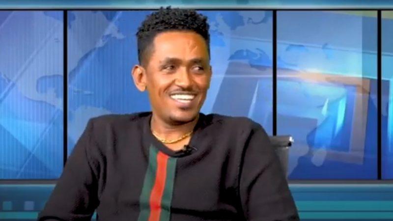 Le musicien Hachalu Hundessa arborant un grand sourire dans un studio de télévision. Il porte son regard sur le côté.