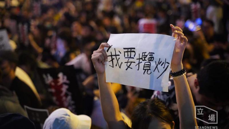 Au milieu d'une foule, on distingue les bras levés d'une femme tenant entre les mains une feuille de papier sur laquelle est inscrit un slogan en caractères chinois.