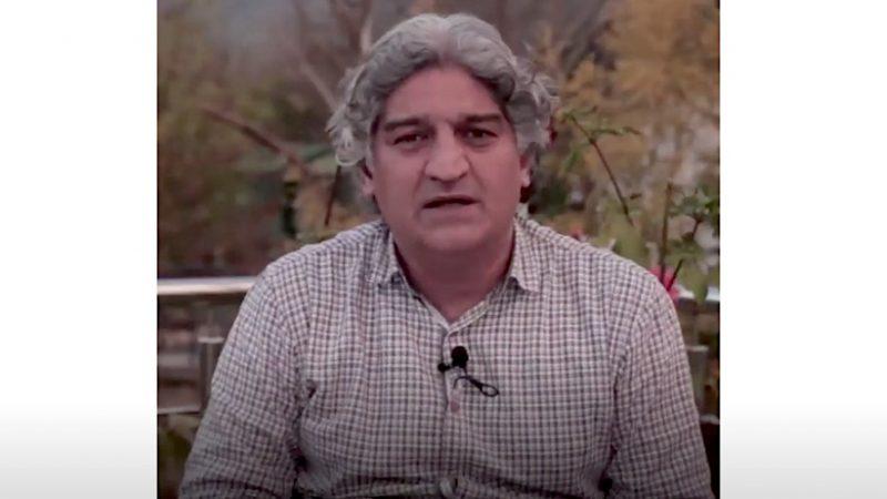 Plan serré du journaliste Matiullah Jan. Il a les cheveux gris et fait face à la camera, lors d'un entretien en plein air.
