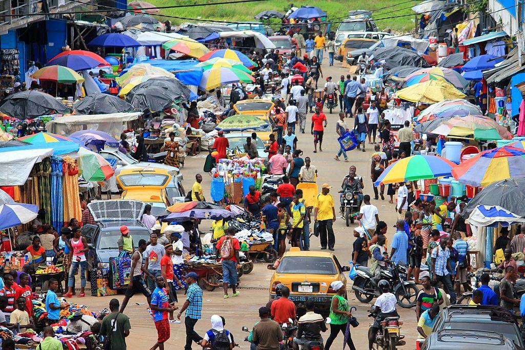 Un marché de Monrovia, où les activités vont bon train. Les étals sont protégés du soleil par des parapluies multicolores.