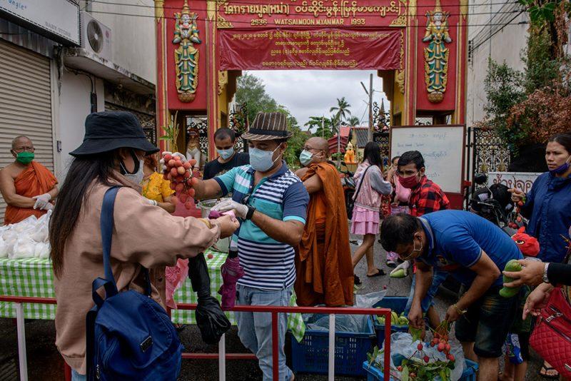 Une femme reçoit des fruits lors d'une distribution à l'entrée d'un temple à Chiang Mai. Les volontaires se tiennent derrière une barrière.