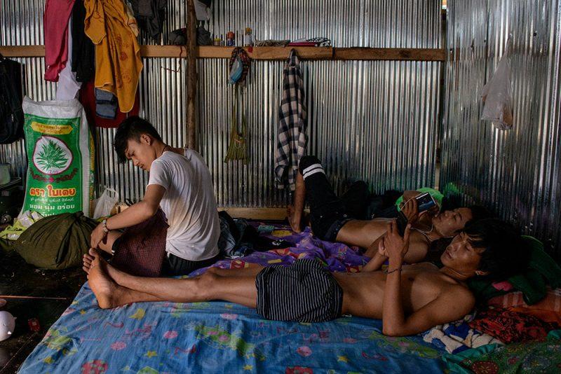 Des ouvriers du bâtiment originaires de Birmanie se reposent dans une cabane de tôle. Deux d'entre eux sont allongés sur un matelas, en train d'utiliser un téléphone portable.
