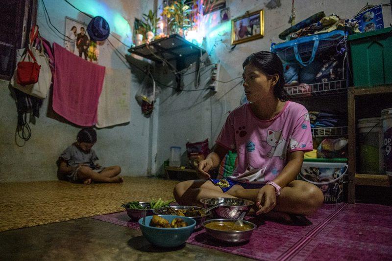 Une travailleuse birmane mange sur un tapis de sol tandis que son enfant est assis dans un coin de la pièce.