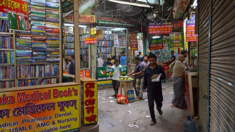 Le marché des livres d'occasion de Nilkhet. De nombreux livres de toutes les couleurs sont entassés sur différents étals.