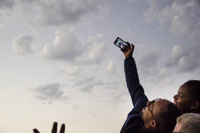 Des jeunes africains prennent un selfie sur fond de ciel nuageux.
