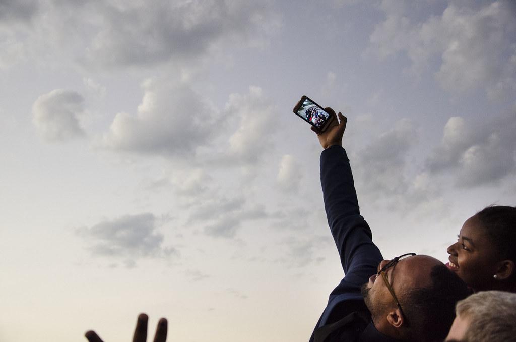 Trois jeunes personnes posent pour un selfie. Un jeune homme brandissant son téléphone et tous lèvent la tête pour la photo, sous un ciel gris.