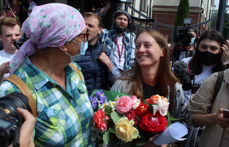 Svetlana Prokopyeva, une journaliste, est devant le tribunal. Une femme devant elle tient une bouquet de fleurs, et autour d'elles se tiennent des caméramans et des photographes