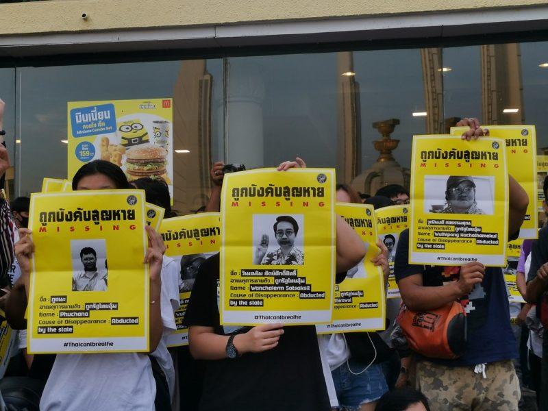 Des membres du Mouvement du printemps ont le visage caché par des affiches jaunes sur lesquelles on voit le portrait et des informations sur une personne disparue.