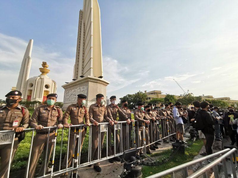 Un cordon de police se tient derrière une barrière, gardant le Monument de la Démocratie. Chaque agent porte un masque de protection faciale et un bérêt noir.