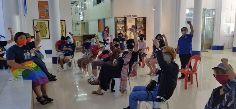 jeunes hommes et femmes masqué·e·s et le poing levé, assis sur des chaises dans une grande salle blanche.