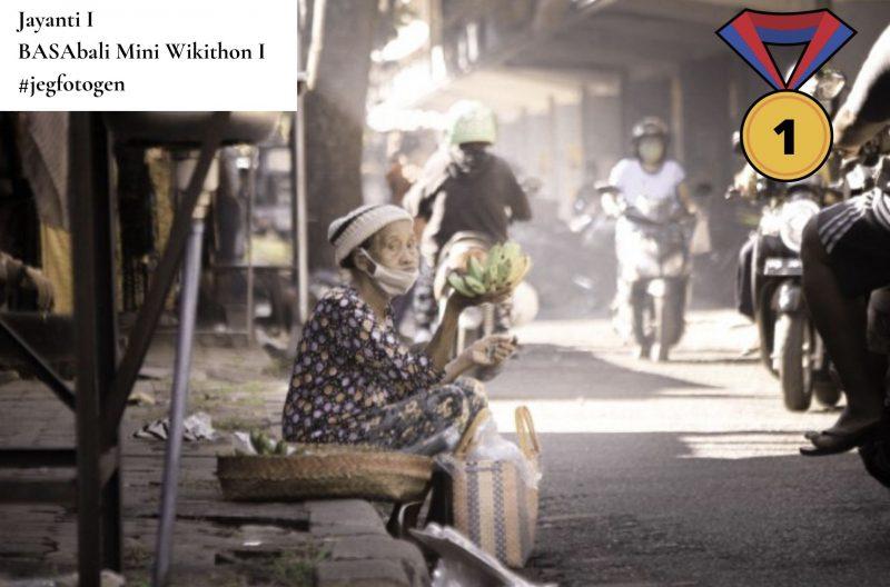 Photo couleur d'une vieille dame assise devant son étal au marché. Elle tient à la main un artichaut pendant que des motocyclistes circulent devant elle, sans s'arrêter.