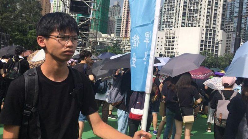 Plan moyen d'un jeune homme asiatique. Il porte un drapeau bleu avec des inscriptions en chinois. Il se trouve parmi des manifestants. Il est vêtu d'un t-shirt noir et porte des lunettes. Derrière lui, on distingue des manifestants, de dos, avec des parapluies. En arrière plan, on aperçoit des buildings. La scène se passe en journée.