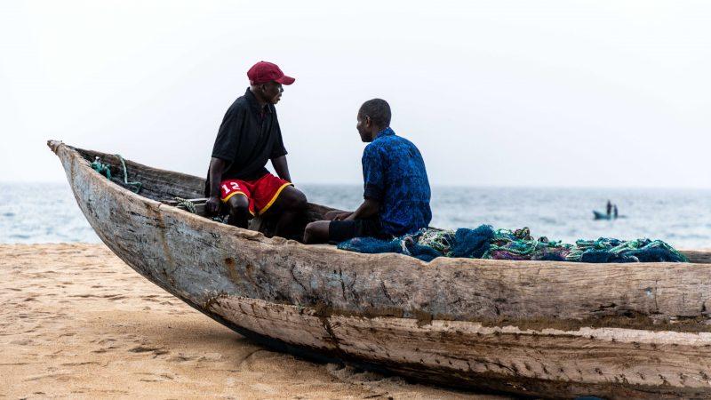 Deux pêcheurs libériens attendent à bord une pirogue posée sur le sable.