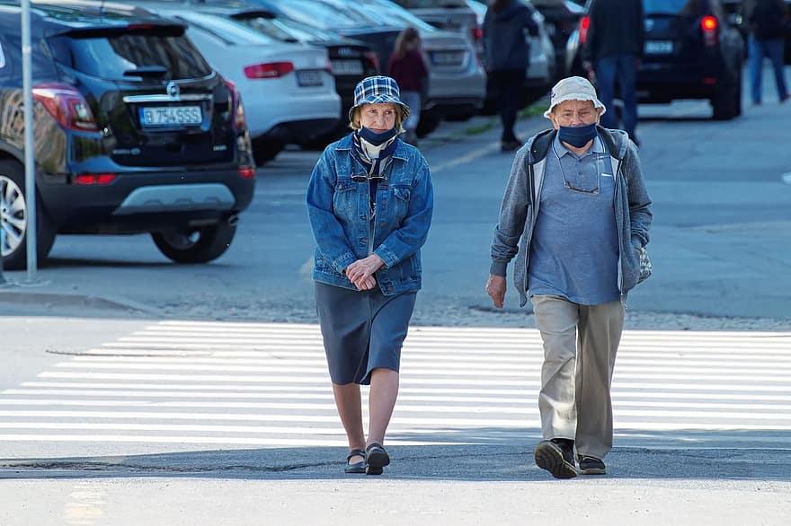 Două persoane în vârstă, un bărbat și o femeie, traversând strada pe trecerea de pietoni. Ambii poartă o pălărie si o mască de protecție facială..
