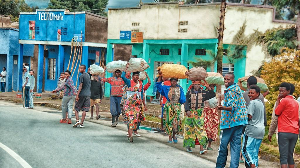 Plusieurs femmes marchent sur une route en portant de gros sacs sur la tête. Des jeunes se retournent, regardant la caméra d'un air amusé.