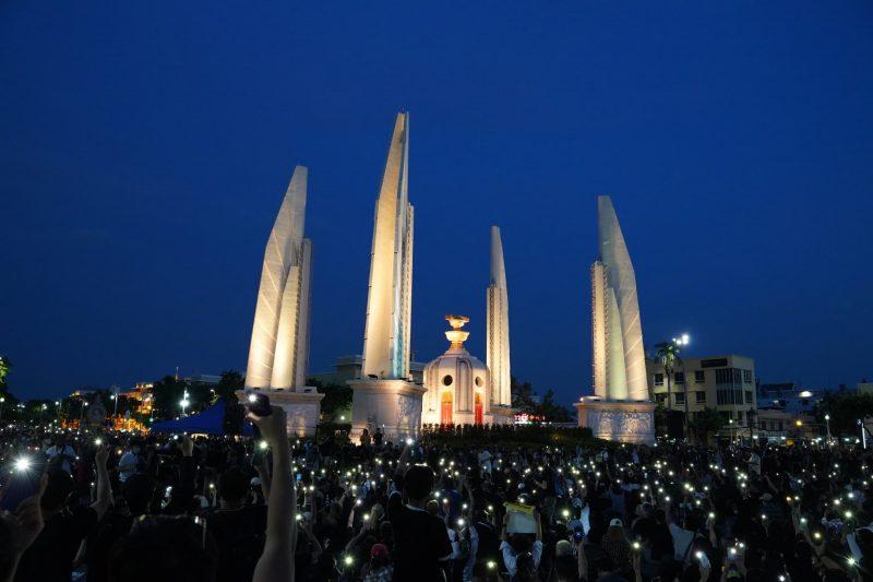 Photo de nuit : le Monument de la Démocratie est éclairé et la foule est parsemée des lumières émises par les téléphones des manifestants.