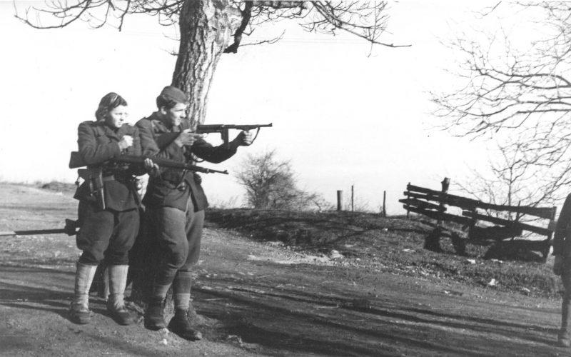 Un couple de partisans yougoslaves s'entraînent au tir dans un champ.
