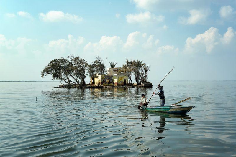 Deux pêcheurs sur une barque en bois naviguent sur les eaux paisibles du lac Burullus en Egypte.