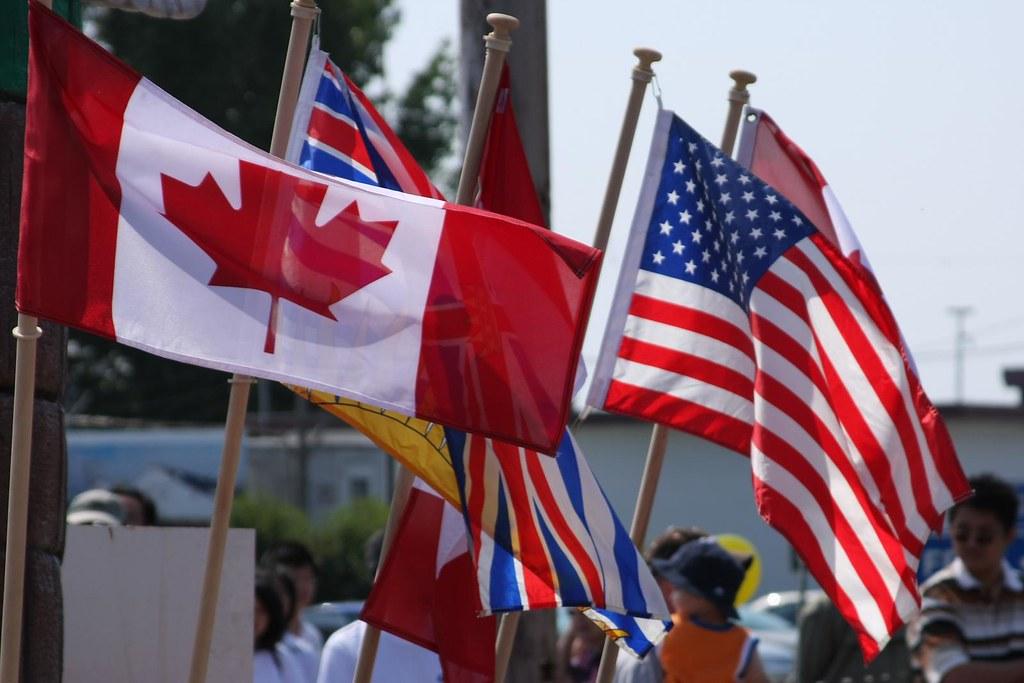 On distingue plusieurs drapeaux, notamment un drapeau canadien et un drapeau américain. En arrière plan, il y a une foule de personnes. Le temps est plutôt beau.