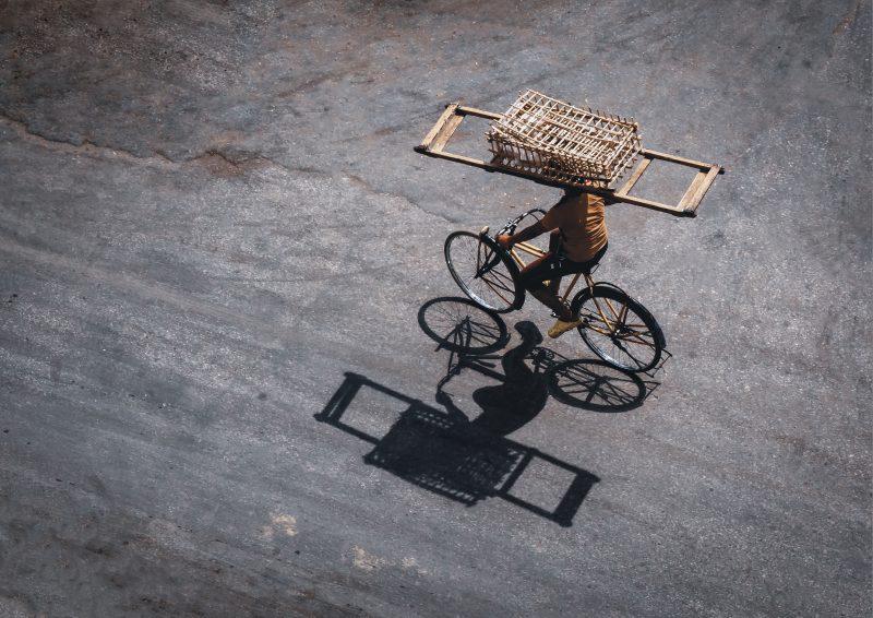 Vue surplombante sur un livreur de pain en Egypte, qui porte un panier sur sa tête et se déplace à vélo.