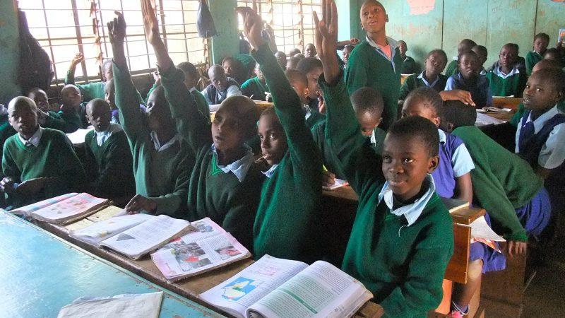 Des élèves de Kibera, dans la capitale du Kenya, Nairobi, lèvent la main lors d'une leçon. La salle de classe est bondée.