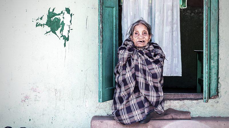 L'image représente une femme agée assise sur le bord d'une fenêtre ouverte. Elle est enveloppée dans un drap à carreau bleu et blanc. Elle a la bouche entre-ouverte et il lui manque quelques dents. Des chaussures sont posées sur sa droite. On distingue des rideaux sur la fenêtre. Un graffiti, de couleur verte, est visible sur le mur.