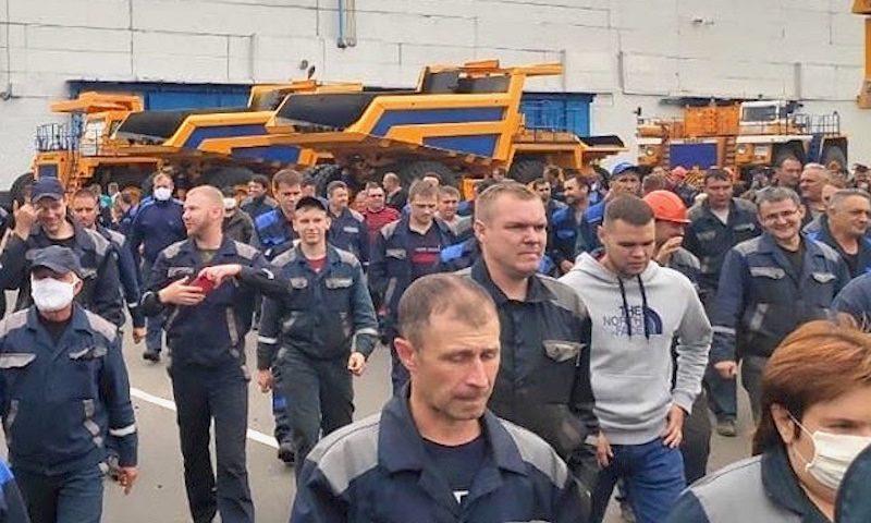 Des hommes, la plupart en tenue de travail bleue, marchent devant un bâtiment.