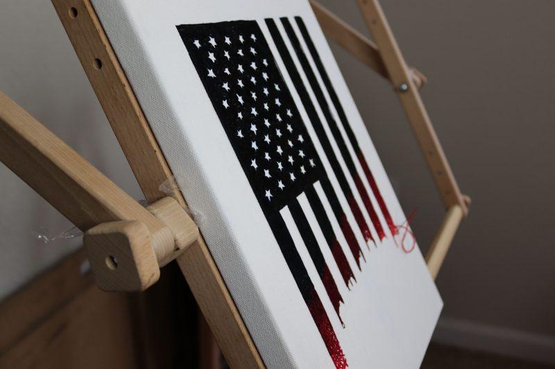 Le tableau en broderie sur toile est posé sur un chevalet. On y voit le drapeau des États-Unis, dont les bandes rouges semblent en cours de finition.