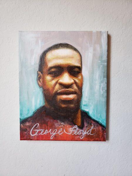 Le visage de George Floyd peint de façon réaliste par Nneka Jones, avec son nom inscrit en bas du tableau. Il a une expression neutre.