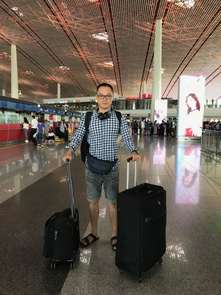 Plan d'un jeune homme chinois se tenant debout dans un aéroport. Il y a deux bagages à ses côtés. Il porte un sac à dos, un sac banane et un casque pour écouter de la musique. Il est vêtu d'un short et chausse des sandales noires. Derrière lui, en arrière plan, on distingue une foule compacte de personnes.