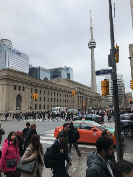 L'image montre un carrefour d'une grande ville où une multitude de personnes se déplacent sur les trottoirs et passages pour piétons. Le ciel est couvert et les gens sont habillés chaudement. On distingue de hauts buildings, quelques voitures et des feux de signalisation.