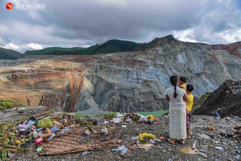 Une femme se tient avec ses deux enfants au bord d'une falaise, face à une colline exploitée pour le jade à Hpakant, Myanmar.