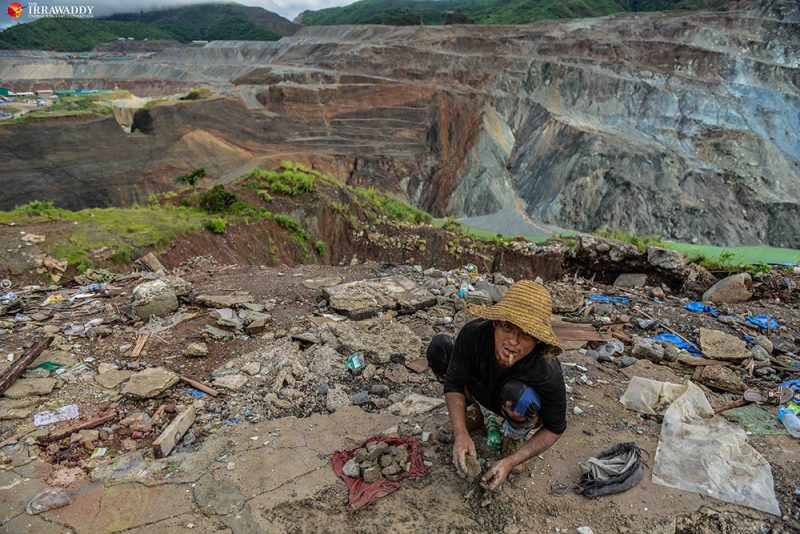 Un mineur est accroupi, en train de trier ses pierres à Hpakant, Myanmar. Derrière lui s'étendent les collines déboisées, exploitées pour leur jade.