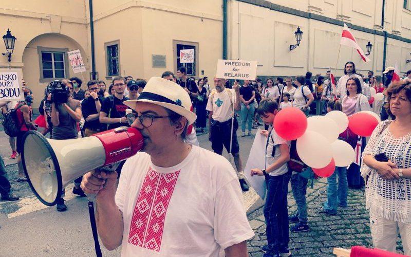 L'écrivain Max Ščur est en tête de cortège, un haut-parleur à la main. Derrière lui défilent des manifestants en blanc et rouge.